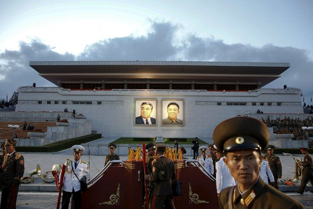 Soldiers and military band pack their stuff before a grand stand decorated with portraits of North Korea's founder Kim Il-sung (L) and former leader Kim Jong-il after the parade celebrating the 70th anniversary of the founding of the ruling Workers' Party of Korea, in Pyongyang October 10, 2015. (Photo by Damir Sagolj/Reuters)