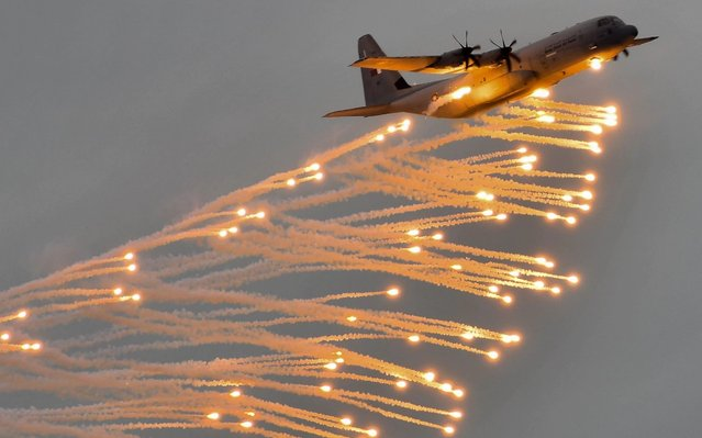 A military aircraft dumps flares during a military parade to mark Qatar's National Day, in Doha, Qatar, 18 December 2019. Qatar National Day marks Qatar's unification and independence in 1878 when Shaikh Jasim, the founder of the State, succeeded his father, Shaikh Muhammad Bin Thani, as the ruler and led the country towards unity. (Photo by Noushad Thekkayil/EPA/EFE)