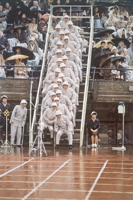 Dressed in rain gear, judges at the 1964 Summer Olympics in Tokyo, Japan, October 14, 1964, assumed these unique positions, each with a place to record, in the track event. (Photo by AP Photo)