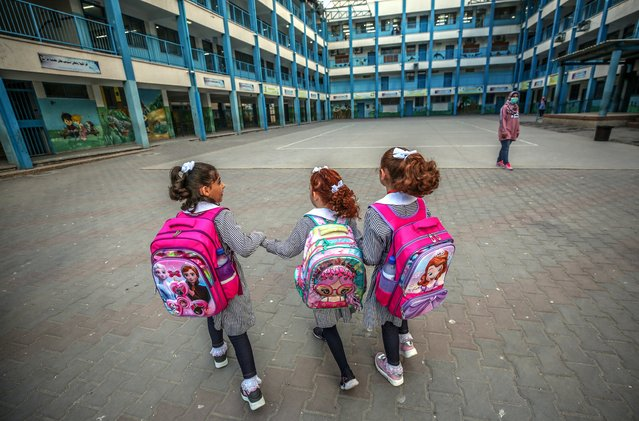 Palestinian girls walk to their school in Gaza City, 09 August 2020. Tens of thousands of children in the besieged Gaza Strip returned to schools on 08 August 2020 after five months of closure as a precaturionary measure against the spreading of the coronavirus disease (COVID-19) pandemic. (Photo by Mohammed Saber/EPA/EFE)