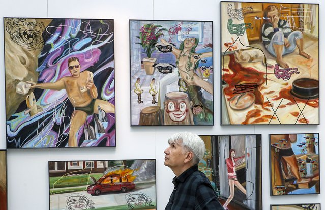 A visitor examines artworks by Ivan Gorshkov during the Cosmoscow international fair in Moscow, Russia, 10 September 2020. More than 200 contemporary artists take part Cosmoscow international fair is an annual contemporary art festival that runs from 10 to 13 September 2020. (Photo by Sergei Ilnitsky/EPA/EFE)