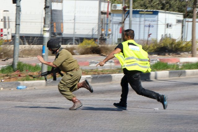 A Palestinian (R) posing as a journalist runs after a wounded Israeli soldier to continue stabbing him before being shot dead near the West Bank city of Hebron October 16, 2015. Palestinians set fire to a Jewish shrine in the occupied West Bank and an attacker disguised as a journalist stabbed an Israeli soldier on Friday as tensions ran high after more than two weeks of violence. (Photo by Bilal al-Taweel/Reuters)