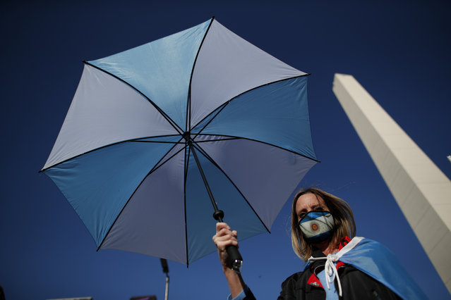 A woman holds an umbrella during a protest against a wide range of issues including government economic policy and state policies to combat the spread of COVID-19, in Buenos Aires, Argentina, Saturday, September 19, 2020. (Photo by Natacha Pisarenko/AP Photo)