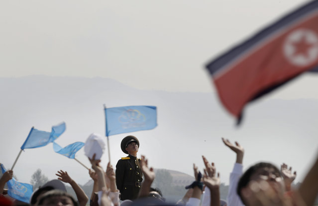 A North Korean military soldier stands guard as North Koreans wave flags and cheer during an aerial display on Saturday, September 24, 2016, in Wonsan, North Korea. (Photo by Wong Maye-E/AP Photo)