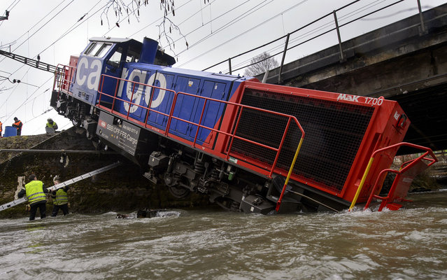 A diesel locomotive has ended up in the river Venoge on March 8, 2013 near Penthalaz, Western Switzerland. The freight locomotive derailed near Cossonez railway station with its driver slightly injured. (Photo by Fabrice Coffrini/AFP Photo)