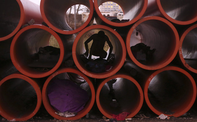 A Filipino man prepares his sleeping area inside a huge water pipe in suburban Pasay, south of Manila, Philippines Tuesday, October 20, 2015. Several homeless people have made the pipes as their temporary shelter. (Photo by Aaron Favila/AP Photo)