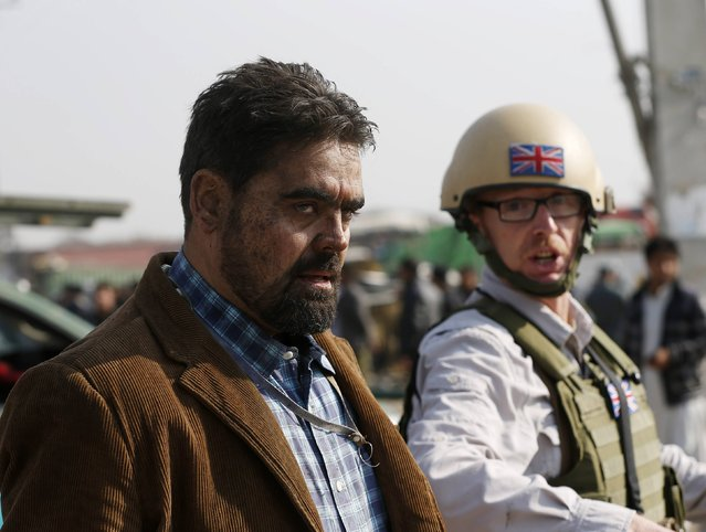 A British security official (R) escorts a survivor from the wreckage of a British embassy vehicle after a suicide attack in Kabul, November 27, 2014. A suicide bomber struck the vehicle in Afghanistan's capital on Thursday, killing at least three people and wounding many bystanders, officials and a Reuters witness said. (Photo by Omar Sobhani/Reuters)