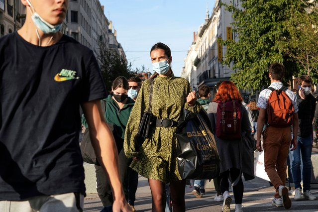 People wearing face masks cross the street in the center of Lyon, central France, Thursday, October 8, 2020. French authorities have placed Lyon on maximum virus alert, banning festive gatherings and requiring all bars to close. (Photo by Laurent Cipriani/AP Photo)