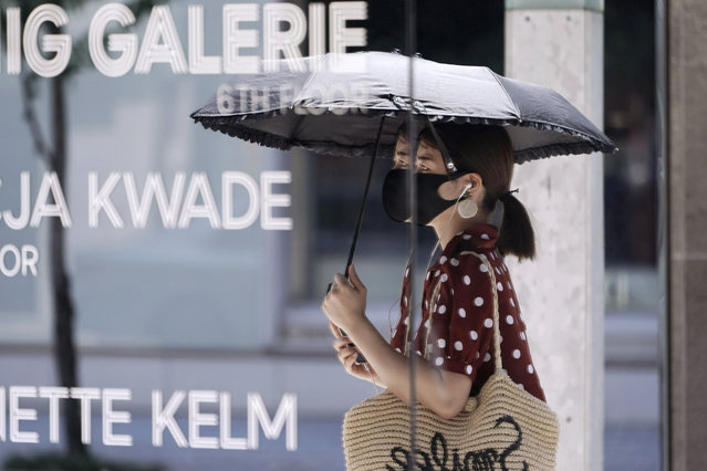 A woman wearing a protective mask to help curb the spread of the new coronavirus is reflected on a mirror window of a shop Wednesday, August 12, 2020, in Tokyo. Hot weather Wednesday has set with temperatures rising up over 34 degrees Celsius (93.2 degrees Fahrenheit) in Tokyo, according to the Japan Meteorological Agency. (Photo by Eugene Hoshiko/AP Photo)