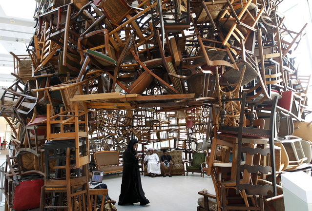 "A visitor walks within an installation titled ""Chairs"", made of wooden chairs by Japanese artist Tadashi Kawamata, during Abu Dhabi Art at Saadiyat island, off the coast of Abu Dhabi, November 7, 2012. (Photo by Jumana El-Heloueh/Reuters)"