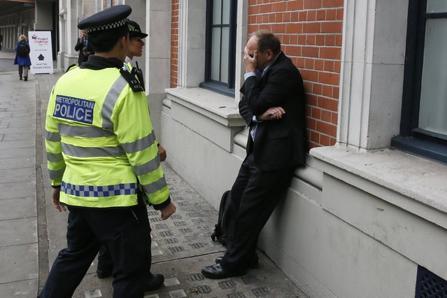 A visitor to the MIPIM property fair reacts as he is detained by police officers following scuffles with housing campaigners outside Olympia exhibition and conference centre in London, in this October 15, 2014 file photo. (Photo by Stefan Wermuth/Reuters)