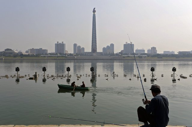 In this Monday, September 24, 2012 photo, a small boat goes by a man fishing along the Taedong River in Pyongyang, North Korea. (Photo by Vincent Yu/AP Photo)