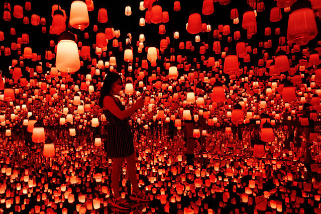 "In this photo taken on October 14, 2020, a woman visits the ""Forest of Lamps"" digital installation room with hanging lamps which illuminate as visitors near them, in the TeamLab Borderless exhibition at Mori Building Digital Art Museum in Tokyo. (Photo by Behrouz Mehri/AFP Photo)"