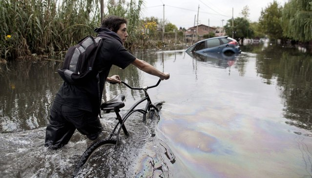 A man pushes his bike through a flooded street in La Plata, in Argentina's Buenos Aires province, Wednesday, April 3, 2013. At least 35 people were killed by flooding overnight in Argentina's Buenos Aires province, the governor said Wednesday, bringing the overall death toll from days of torrential rains to at least 41 and leaving large stretches of the provincial capital under water. (Photo by Natacha Pisarenko/AP Photo)