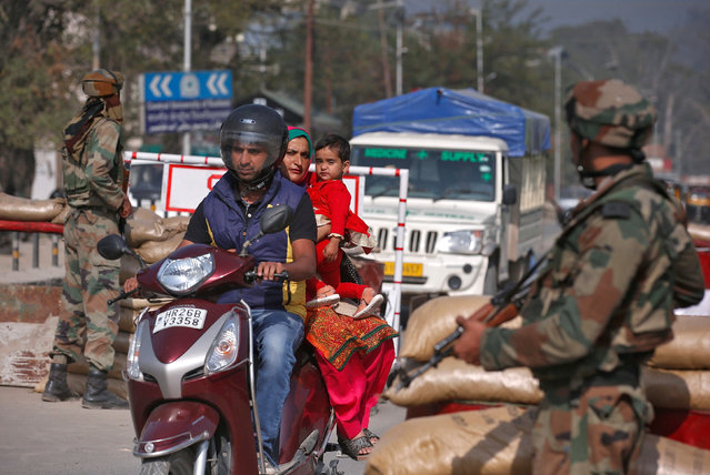 Commuters move past Indian army soldiers standing guard at a temporary check point near their headquarters in Srinagar October 6, 2016. (Photo by Danish Ismail/Reuters)