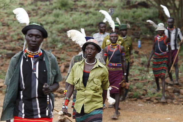Pokot men walk towards the home of a girl to be taken as wife for a member of their group, about 80 km (50 miles) from the town of Marigat in Baringo County December 7, 2014. (Photo by Siegfried Modola/Reuters)