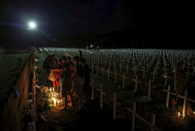 Residents pray at the graves of their loved ones at a mass grave for Typhoon Haiyan victims on All Saints Day in Tacloban city in central Philippines November 1, 2015. (Photo by Erik De Castro/Reuters)
