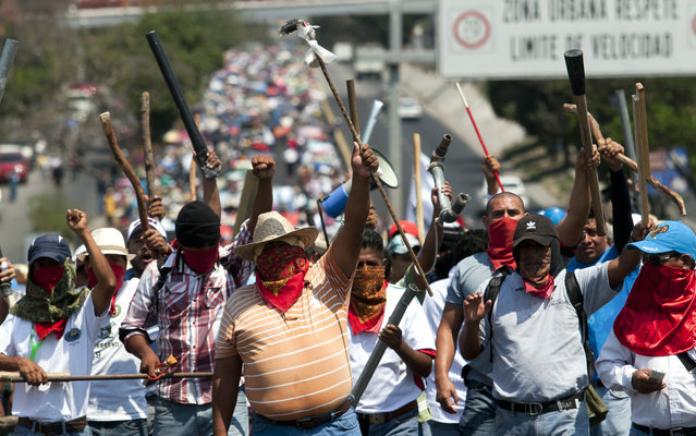 Teachers members of the National Coordinating Committee of Education Workers (CNTE) march along the highway between Mexico City and Acapulco in Chilpancingo, Guerrero state, Mexico on April 18, 2013. The teachers protest against the educational reform proposed by the government. (Photo by Pedro Pardo/AFP Photo)
