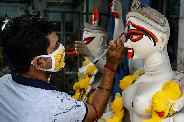 An artist wearing a face mask as a precautionary measure against the coronavirus paints a clay idol of Hindu goddess Kali inside his studio ahead of the Kali Puja festival in Kolkata, India, Friday, November 6, 2020. (Photo by Bikas Das/AP Photo)