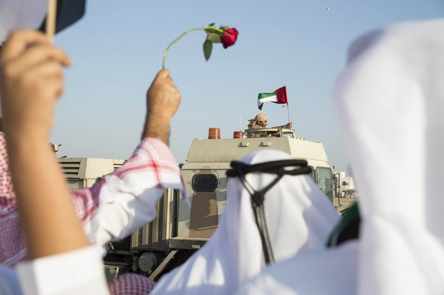 A member of the United Arab Emirates armed forces waves a UAE flag as the first batch of UAE military personnel returns from Yemen in Abu Dhabi, November 7, 2015. (Photo by Reuters/United Arab Emirates News Agency WAM)