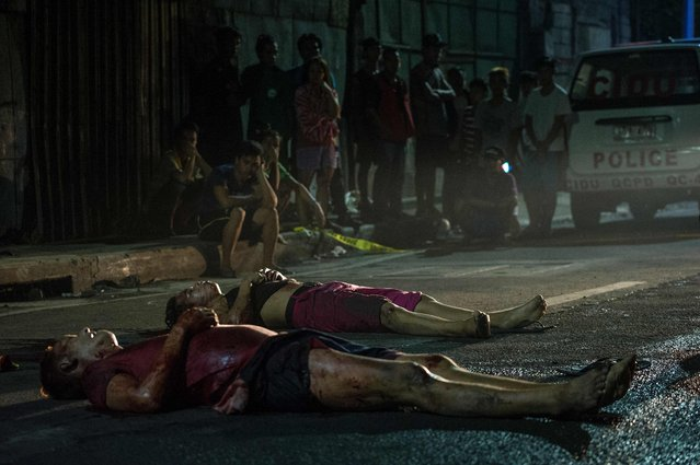 Residents look at two dead bodies lying on the road after they were gunned down by unidentified men riding a motorcycle in Manila on October 3, 2016. (Photo by Noel Celis/AFP Photo)