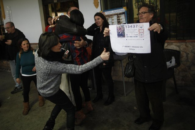 """A lottery seller (R) holds a sign with the winning number of Spain's Christmas Lottery """"El Gordo"""" next to winners as they celebrate in Arriate, near Malaga, southern Spain December 22, 2014. (Photo by Jon Nazca/Reuters)"""