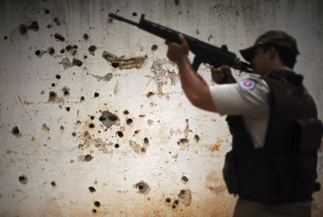 "Police patrol past the ""rifle wall"" pockmarked by bullets from many shootouts between drug gangs and police, in the Nordeste de Amaralina slum complex in Salvador, Bahia State, March 28, 2013. One of Brazil's main tourist destinations and a 2014 World Cup host city, Salvador suffers from an unprecedented wave of violence with an increase of over 250% in the murder rate, according to the Brazilian Center for Latin American Studies (CEBELA). (Photo by Lunae Parracho/Reuters)"