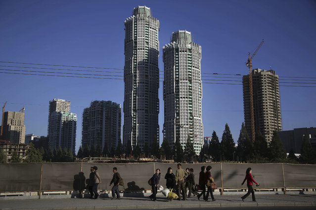 """North Korean men and women walk past buildings under construction on """"Ryomyong Street"""", Monday, October 17, 2016, in Pyongyang, North Korea, where North Korean leader Kim Jong Un has put his soldier-builders to work on yet another major project – a series of apartments and high-rises that are once again changing the Pyongyang skyline. """"Ryomyong Street"""", is to have the country's tallest apartment building, at 70 stories, along with a 50-story building and a handful of smaller ones in the 30-40 story range. (Photo by Wong Maye-E/AP Photo)"""