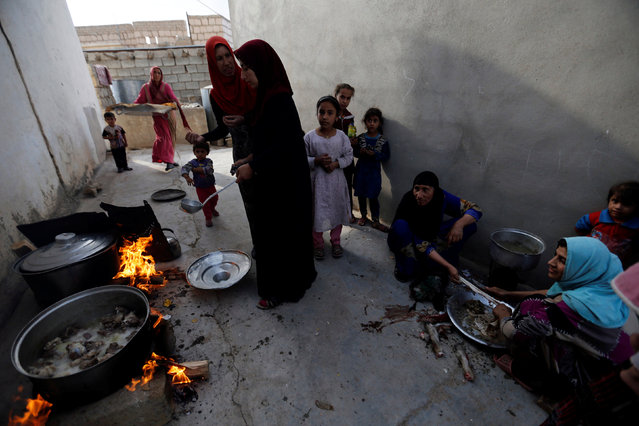 Civilians cook for the Iraqi army after the liberation of Khalidiya village from Islamic State militants, south of Mosul, during an operation to attack Islamic State militants in Mosul, Iraq, October 20, 2016. (Photo by Thaier Al-Sudani/Reuters)