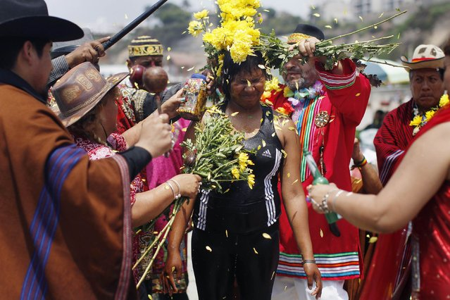 A woman receives a shower of flower petals by shamans performing a ritual, as they offer predictions for the new year at Agua Dulce beach in Lima December 29, 2014. The ritual is an end-of-the-year tradition and the shamans used the chance to ask for world peace and better relations between the U.S. and Cuba for 2015. (Photo by Enrique Castro-Mendivil/Reuters)