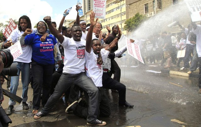 Protestors react to a riot police water cannon as they participate in a demonstration against lawmakers' salary demands outside the parliament buildings in the capital Nairobi, May 14, 2013. Kenyan police in riot gear fired teargas and water cannons on Tuesday to disperse about 200 protesters gathered outside parliament to demonstrate against lawmakers' salary demands. (Photo by Thomas Mukoya/Reuters)