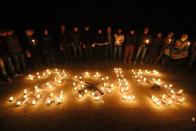 Activists stand over pictures of war victims under candles in a new year event in Salah al-Din neighbourhood in central Aleppo December 31, 2014. (Photo by Hosam Katan/Reuters)