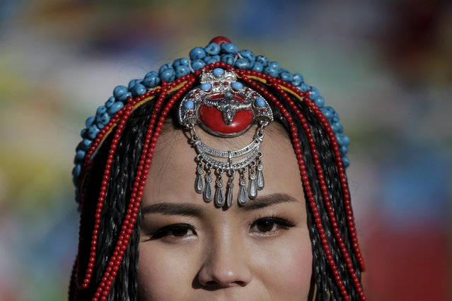 Jing Li wears a Tibetan traditional costume as she gets ready for her wedding photo to be taken at the Nianqing Tanggula mountain pass in the Tibet Autonomous Region, China November 18, 2015. Jing, 22, and her husband Ke Xu, 23, both from Shiyan in northwestern Hubei province live in Tibet for three year. The couple married last month. (Photo by Damir Sagolj/Reuters)