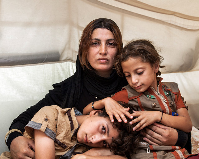 Amira and her Children by Ivor Prickett – £1,000 fourth prize winner. Prickett took this photograph in northern Iraq in September 2014 when he was working on an assignment for UNHCR. Prickett says: 'I met Amira and her family in the tent they were living in at the Baharka camp near Erbil; they had fled their village near Mosul after Isis had taken control of the area. (Photo by Ivor Prickett/Taylor Wessing Portrait Prize 2015)