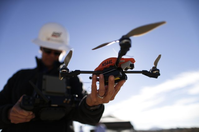 In this October 16, 2014 picture, former Navy helicopter pilot and San Diego Gas & Electric unmanned aircraft operator Teena Deering holds a drone as it is prepared for takeoff near Boulevard, Calif. San Diego Gas and Electric thinks that drones might be a cheaper, faster way to inspect its power lines in remote areas. (Photo by Gregory Bull/AP Photo)