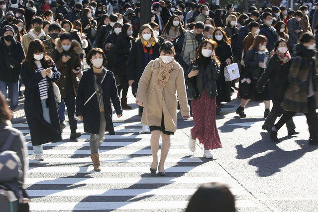 People wearing face masks to help curb the spread of the coronavirus walk around the scrambled intersection at the Shibuya shopping district in Tokyo Saturday, December 26, 2020. Tokyo has confirmed 949 new cases of the coronavirus on Saturday, a record high for the Japanese capital, as the country struggles with an upsurge that is spreading nationwide. (Photo by Kyodo News via AP Photo)