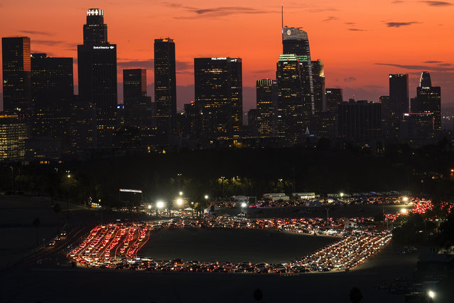 Motorists wait in lines to take a coronavirus test in a parking lot at Dodger Stadium, Monday, January 4, 2021, in Los Angeles. (Photo by Ringo H.W. Chiu/AP Photo)