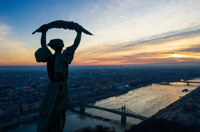 The sun rises behind the Liberty Statue on the top of Gellert Hill, a landmark of the Hungarian capital, in Budapest, Hungary, 27 December 2020. (Photo by Balazs Mohai/EPA/EFE)