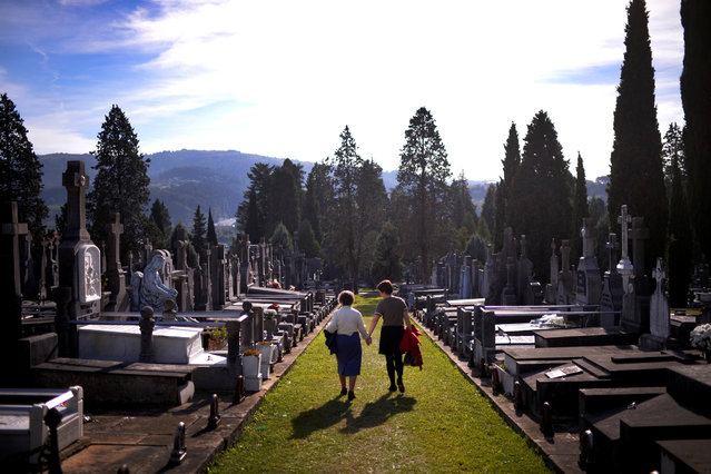 Women walk past graves on All Saints' Day at Derio cemetery near Bilbao, Spain, November 1, 2016. (Photo by Vincent West/Reuters)
