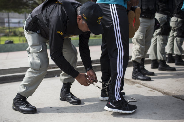 A prison guard takes the shackles off an inmate member of a football team before entering San Juan de Lurigancho prison, in Lima, Peru, Thursday, May 24, 2018. (Photoby Rodrigo Abd/AP Photo)