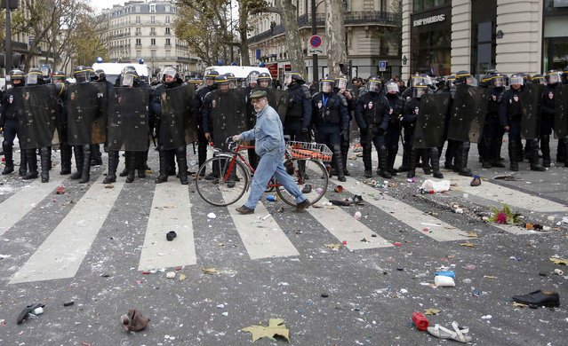 A man with a bicycle walks past CRS riot policemen after clashes with demonstrators at the Place de la Republique after the cancellation of a planned climate march following shootings in the French capital, ahead of the World Climate Change Conference 2015 (COP21), in Paris, France, November 29, 2015. (Photo by Eric Gaillard/Reuters)