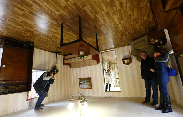 Tourists take photos inside an upside-down house in a tourist complex, near the village of Dukora, Belarus, December 2, 2015. (Photo by Vasily Fedosenko/Reuters)