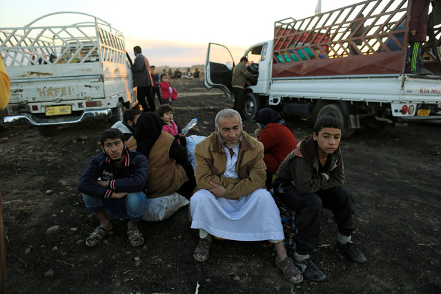 People who had just fled Kokjali near Mosul sit after they arrived at a Peshmerga checkpoint east of Mosul, Iraq November 3, 2016. (Photo by Zohra Bensemra/Reuters)