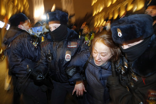 Police officers detain a Navalny supporter during a protest in St. Petersburg, Russia, Tuesday, February 2, 2021. A Moscow court has ordered Russian opposition leader Alexei Navalny to prison for more than 2 1/2 years on charges that he violated the terms of his probation while he was recuperating in Germany from nerve-agent poisoning. Navalny, who is the most prominent critic of President Vladimir Putin, had earlier denounced the proceedings as a vain attempt by the Kremlin to scare millions of Russians into submission. (Photo by Dmitri Lovetsky/AP Photo)