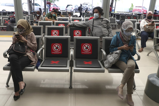 People sit spaced apart as they wait for a coronavirus test required to board long-distance trains the at Senen Train Station in Jakarta, Indonesia, Tuesday, February 9, 2021. (Photo by Tatan Syuflana/AP Photo)
