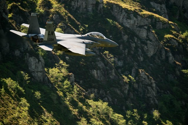"""A United States Air Force (USAF) F-15 fighter jet travels at low altitude through the """"Mach Loop"""" series of valleys near Dolgellau, north Wales on June 26, 2018. The Mach Loop valleys, situated between Dolgellau and Machynlleth, are regularly used by the military for operational low flying training which can take place as low as 76 metres from the nearest terrain. (Photo by Oli Scarff/AFP Photo)"""
