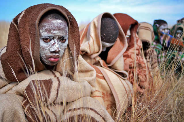 Boys from the Xhosa tribe who have undergone a circumcision ceremony sit near Qunu on June 30, 2013. Qunu is where former South African President Nelson Mandela grew up. Mandela, who turns 95 next month, was rushed to hospital over three weeks ago with a recurrent lung disease. (Photo by Carl De Souza/AFP Photo)