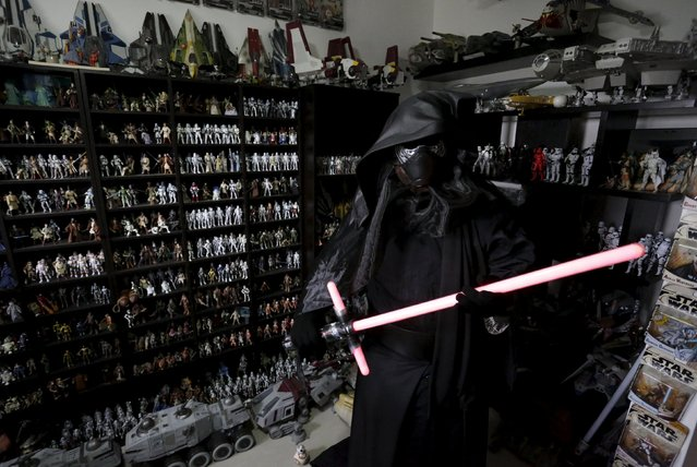 Mexican collector Pablo Perez, dressed as Star Wars character Kylo Ren, poses next to a toy collection of Star Wars characters and items at his home in Monterrey, Mexico December 12, 2015. (Photo by Daniel Becerril/Reuters)