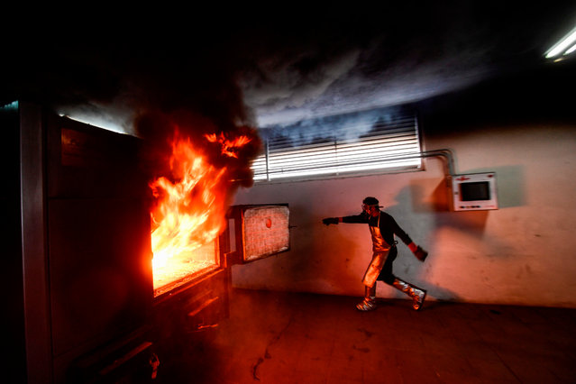 An employee closes the cremation oven during the cremation of the body of a victim of COVID-19 at the Nezahualcoyotl Municipal Cemetery, Mexico state, Mexico, on January 20, 2021. Mexico has officially recorded more than 140,000 Covid-19 deaths – the world's fourth-highest toll after the United States, Brazil and India. (Photo by PPedro Pardo/AFP Photo)