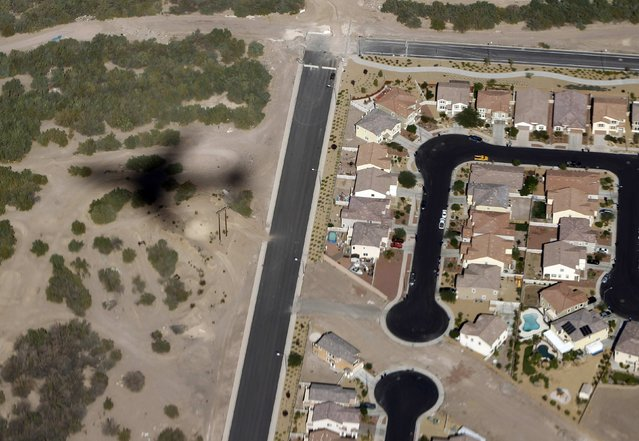 The shadow of Air Force One is cast on the Nevada Desert as it flies past a housing development before touching down in Las Vegas, in this October 24, 2011 file photo. (Photo by Jason Reed/Reuters)